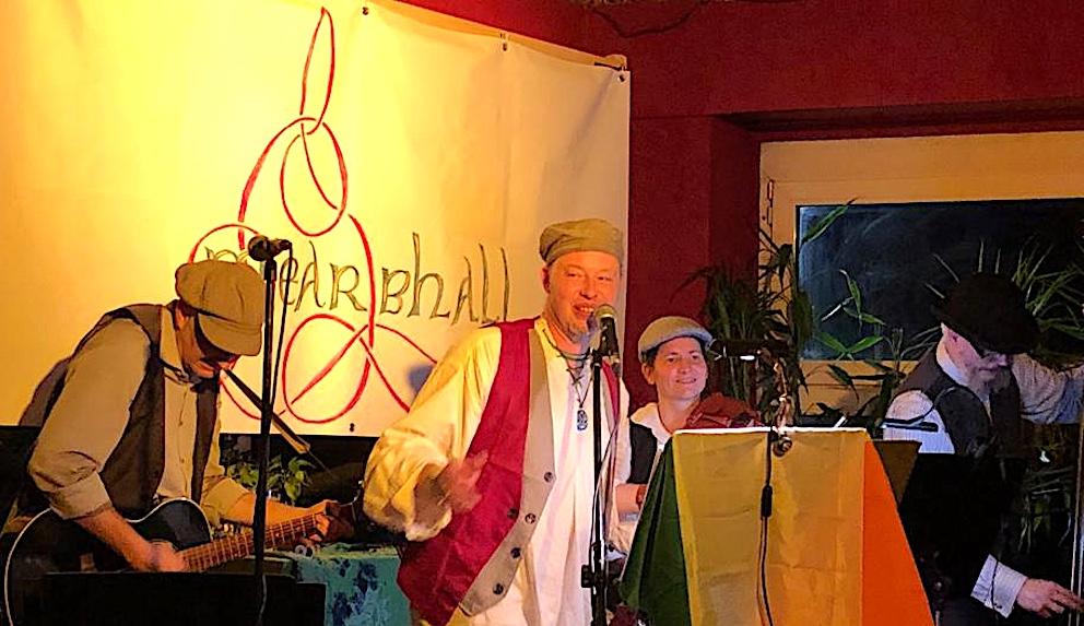 Andreas und Jochen an Gitarre und Bass vertieft in spielen. Véronique wartet auf ihren Geigeneinsatz, Ingo lacht ins Publikum. Warm rote Atmosphäre im Spunk, Wuppertal. Über dem Notenständer hängt die Flagge der Republik Irland.