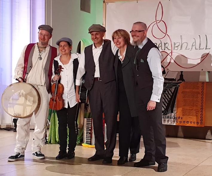 Von links nach rechts sieht man Ingo mit Bodhran, Véronique mit Geige, Andreas, die Pfarrerin Jutta,Degen und Jochen zusammenstehend im Altarbereich den Zuschauern zulächelnd. Im Hintergrund das Mearbhall Banner.