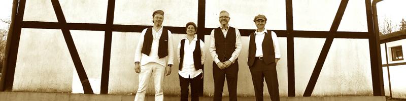 Die Band Mearhall steh vor einem Fachwerkhaus nach einem KOnzert in Hattingen. Alles ist schwarz/ weiß/ sepia.